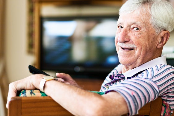 Laughing 90-year-old old man is happily relaxing by watching television, smiling over his shoulder at camera as he holds the remote control, in charge of everyone's viewing! Copy space on the defocused TV screen.